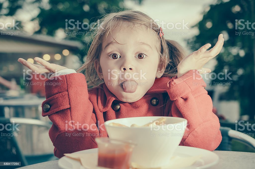 Cute little girl sticking out her tongue while eating stock photo