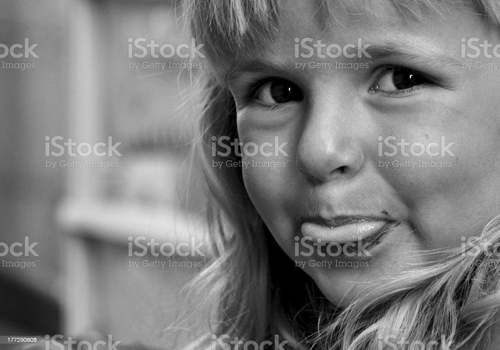 Cute little girl sticking out tongue. Black and White stock photo