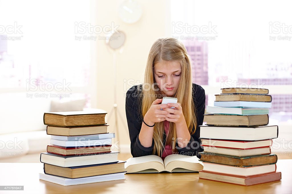Cute little girl texting while studying royalty-free stock photo