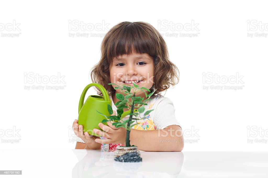 Cute little girl watering the tree stock photo