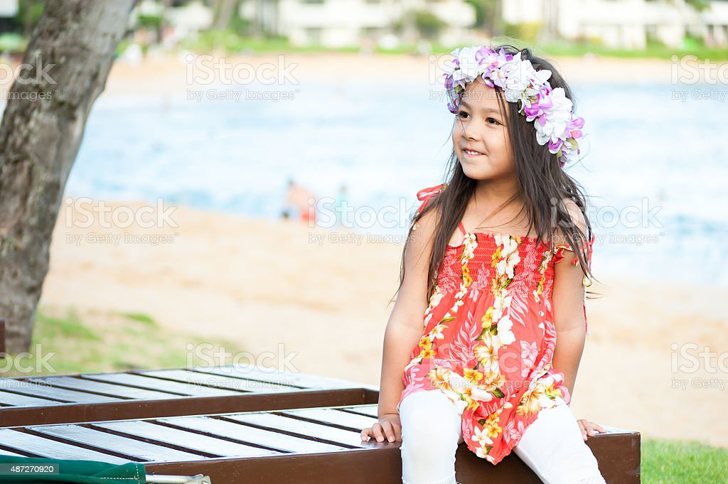 Cute little girl wearing a lei on a Hawaiian beach stock photo