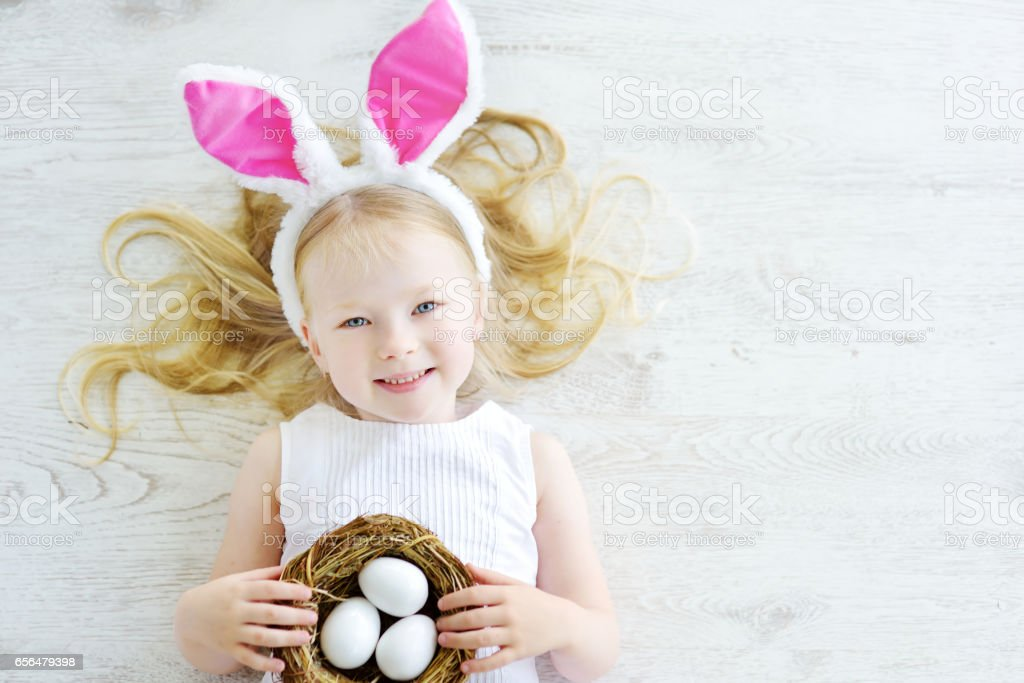 Cute little girl wearing bunny ears playing egg hunt on Easter stock photo
