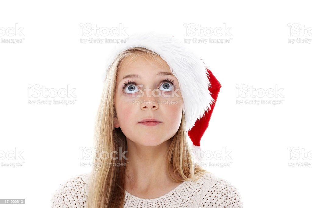 Cute little girl wearing Santa hat looking up at copyspace royalty-free stock photo