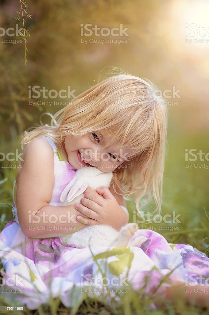 Cute little girl with a bunny rabbit has a easter stock photo