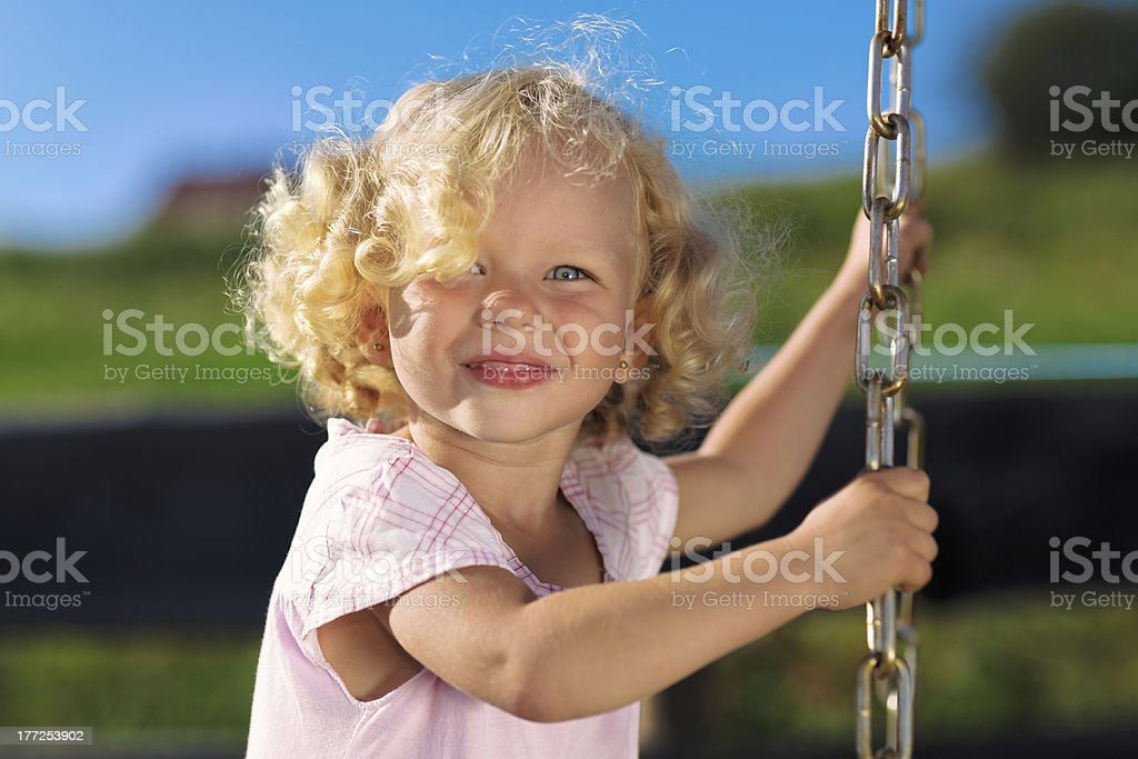 Cute little girl with blond curly hair playing stock photo