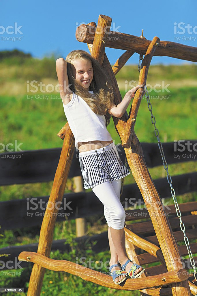Cute little girl with blond long hair playing outdoor stock photo