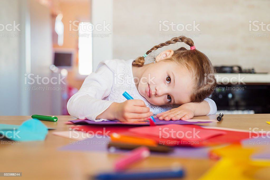 Cute little girl with braids drawing on colorful papers stock photo