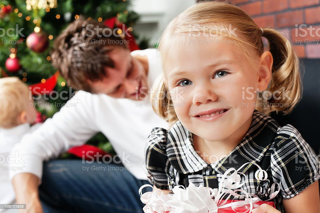 Cute Little Girl With Christmas Present and Family in Background royalty-free stock photo