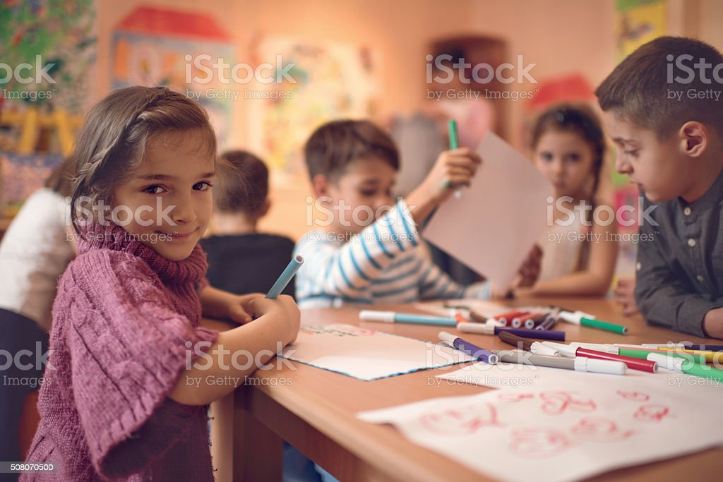Cute little girl with her friends in a preschool. stock photo