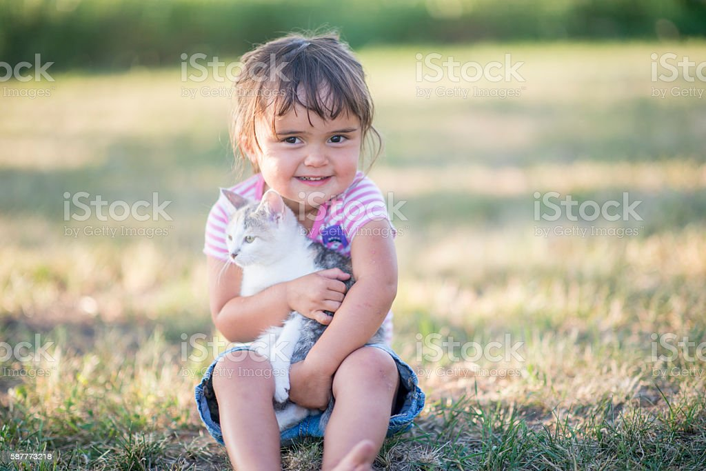 Cute Little Girl with Her Kitten stock photo