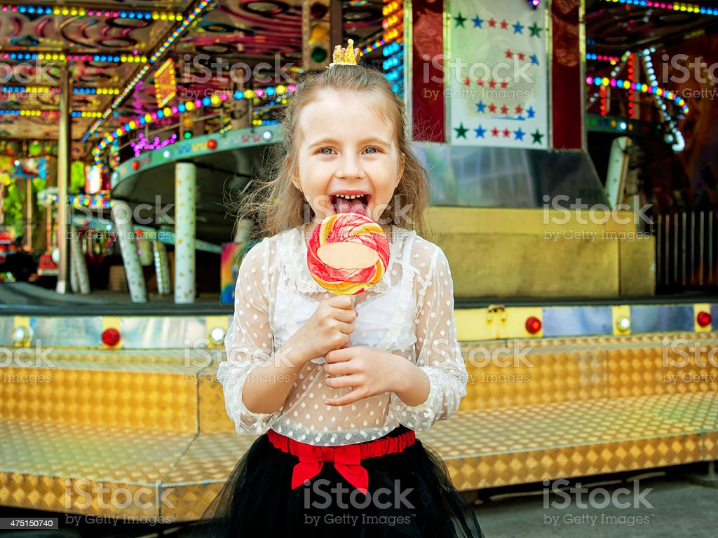 cute little girl with lollipop at amusement park stock photo