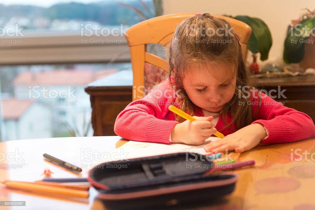 Cute Little Girl with Long Hair Drawing in the Room stock photo