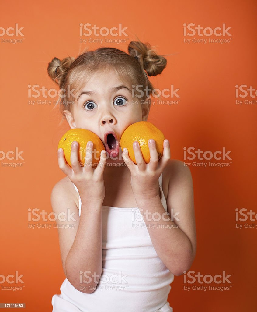 Cute Little Girl with Oranges on Orange Background royalty-free stock photo