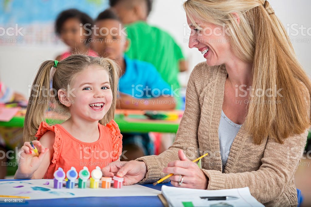 Cute little girl with pigtails laughing while painting in daycare stock photo