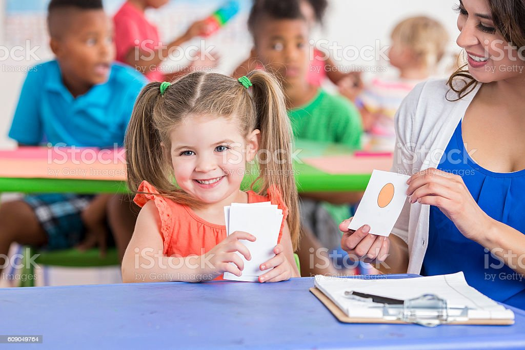 Cute little girl working on flashcards with daycare teacher stock photo