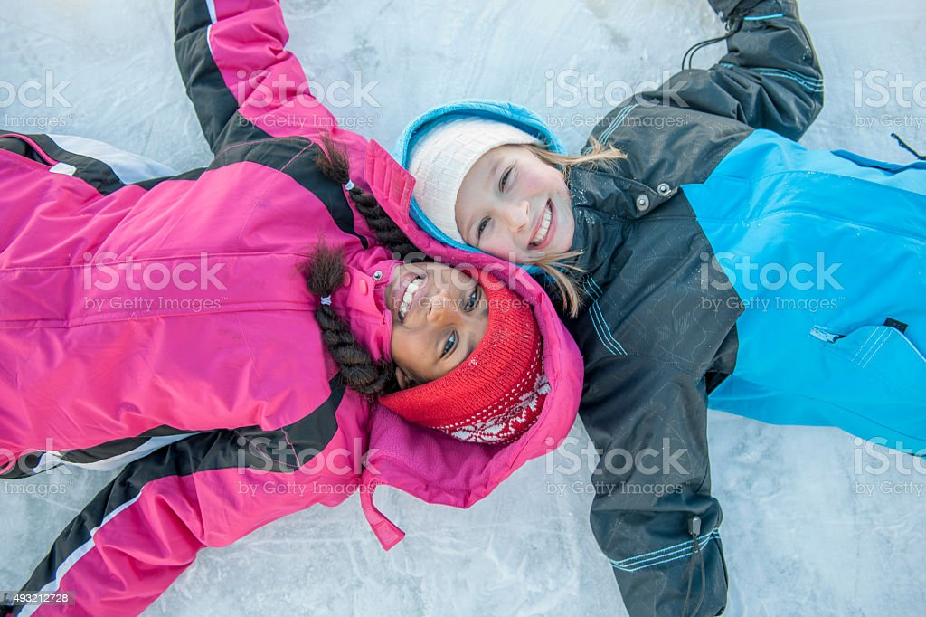 Cute Little Girls Lying on the Ice stock photo