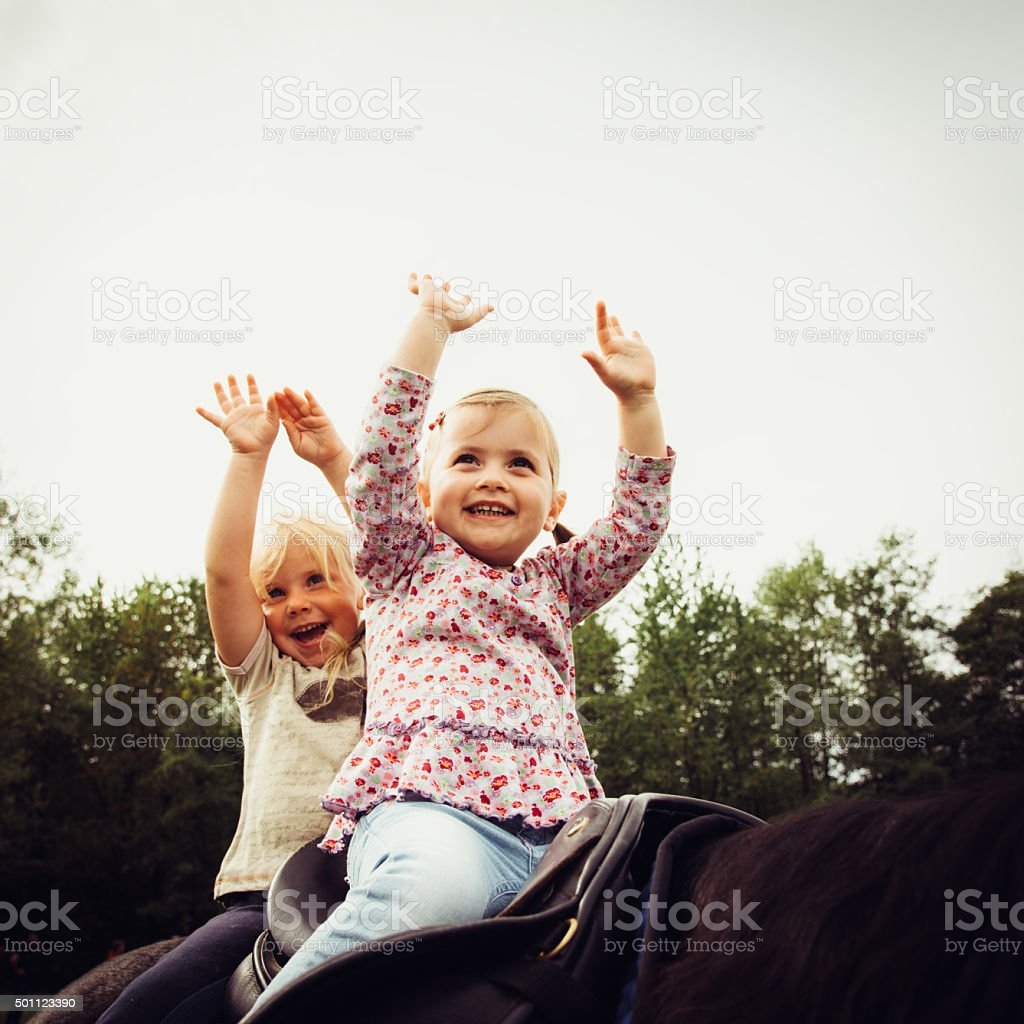 Cute little girls smiling while learning horseback riding stock photo