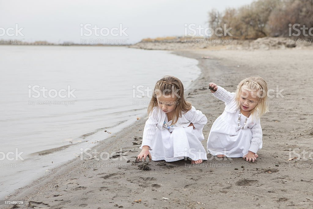 Cute Little Girls Wearing White Dresses Playing on Beach royalty-free stock photo