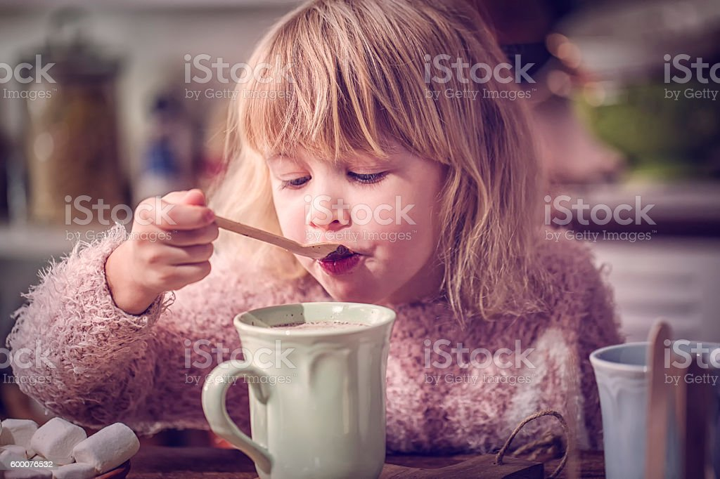 Cute Little Gril Preparing Hot Chocolate Bar with Spoon stock photo
