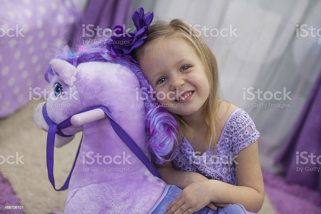 Cute little happy girl playing with toy horse at home royalty-free stock photo