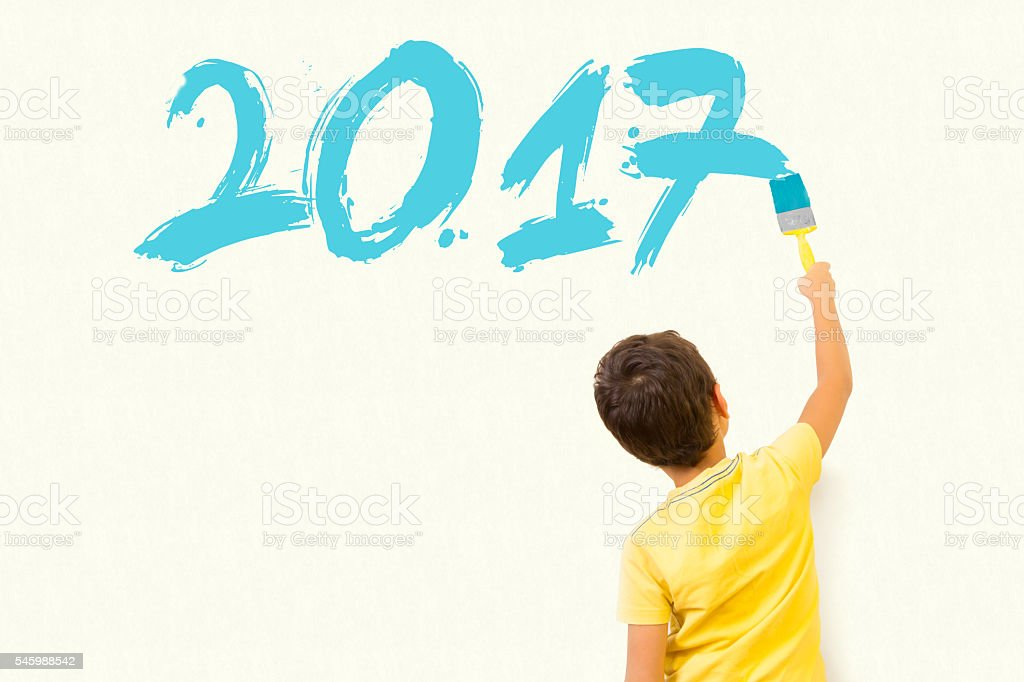 Cute little kid drawing new year 2017 stock photo