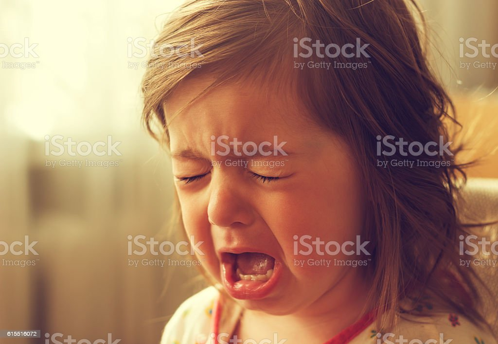 Cute little kid is crying. Toned stock photo
