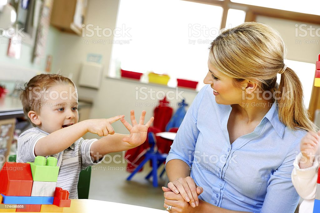 Cute little kid with teacher playing in play room stock photo