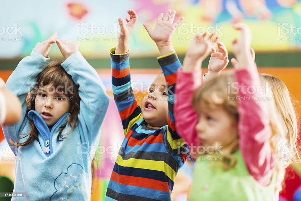 Cute little kids dancing with raised arms stock photo