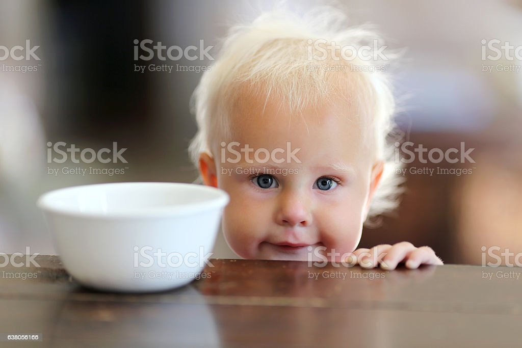 Cute Little One Year Old Baby Girl Next to Cereal stock photo