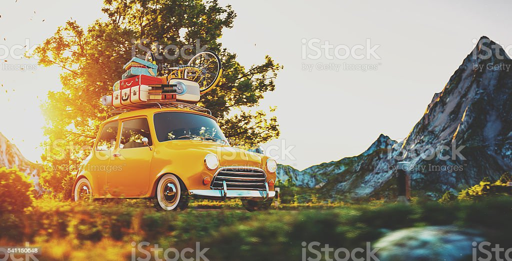 Cute little retro car goes by countryside road at sunset stock photo