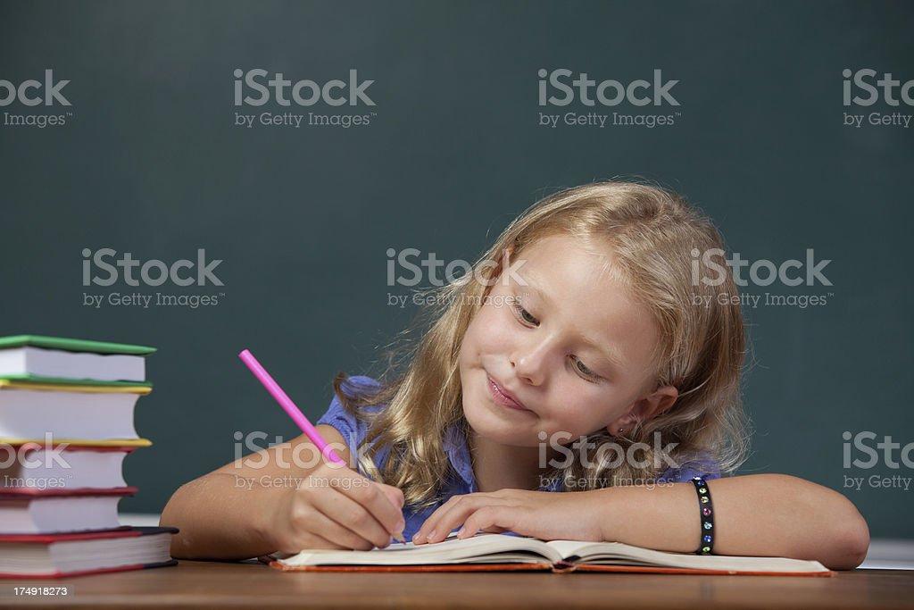 Cute little school girl writing on desk before blackboard royalty-free stock photo