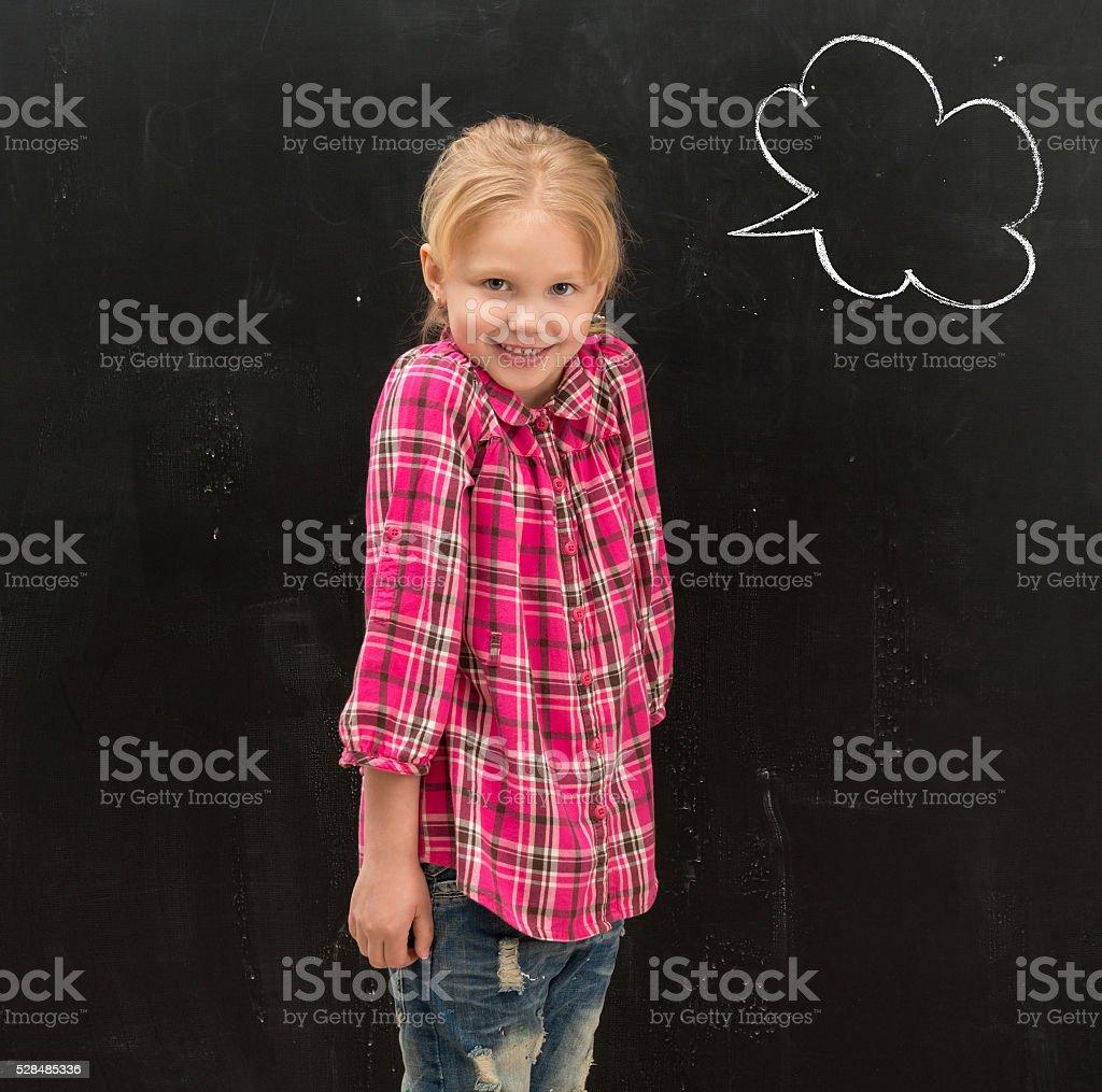 cute little schoolgirl standing in front of the blackboard with stock photo