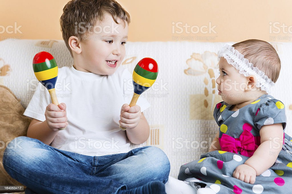 Cute little sister and her brother sitting with maracas stock photo