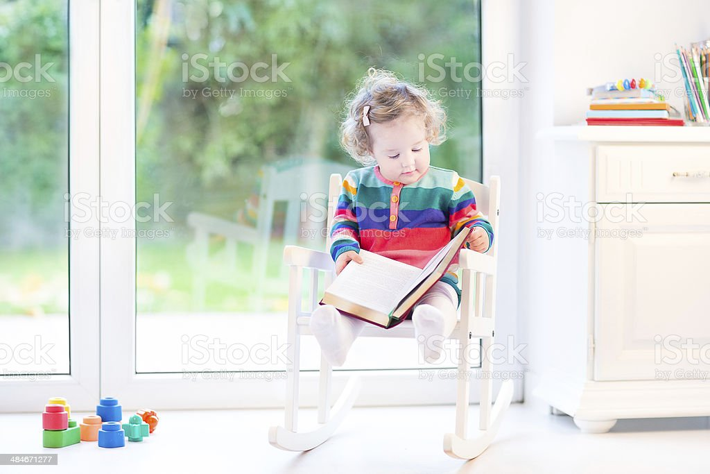 Cute little toddler girl reading book in white rocking chair stock photo
