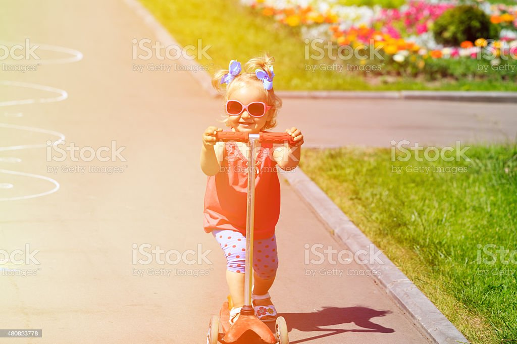 cute little toddler girl riding scooter in the city stock photo