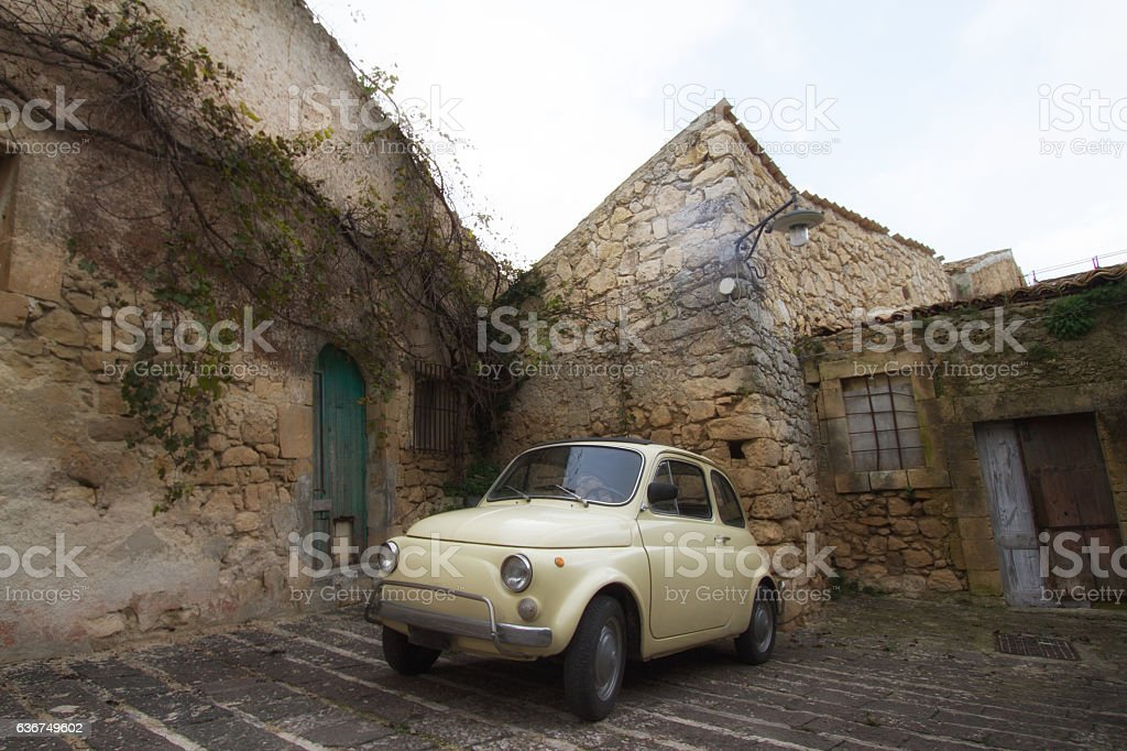 Cute Little Yellow Vintage Car on Ancient Cobbled Street stock photo