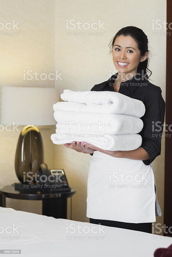 Cute maid holding towels for washing stock photo