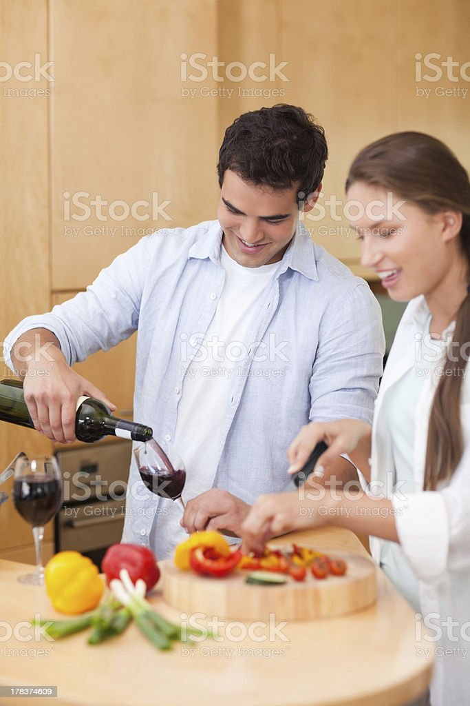 Cute man pouring wine while his wife is cooking royalty-free stock photo