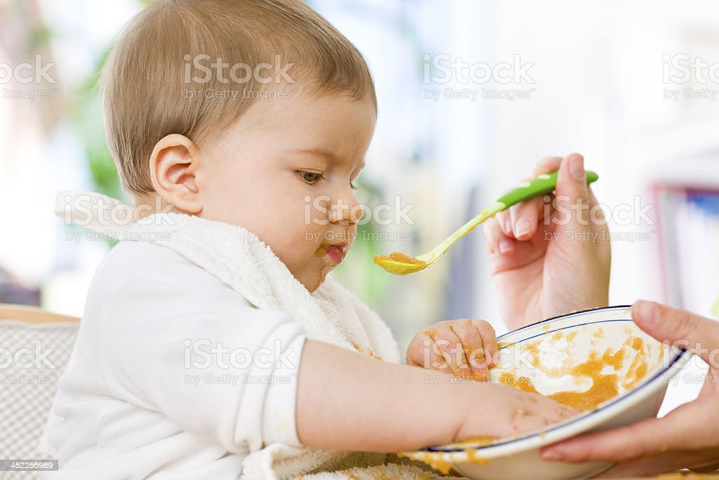 Cute messy baby boy playing with food while eating. stock photo