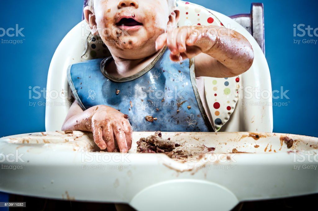 A one year old child sitting in a highchair and covered with his...