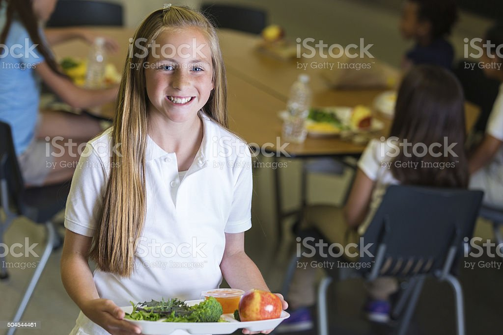 Cute middle school age girl holding tray of cafeteria food stock photo