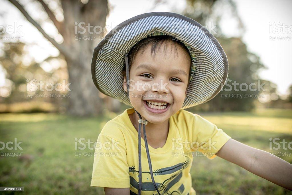 Cute mixed race Asian Caucasian boy plays in a park stock photo