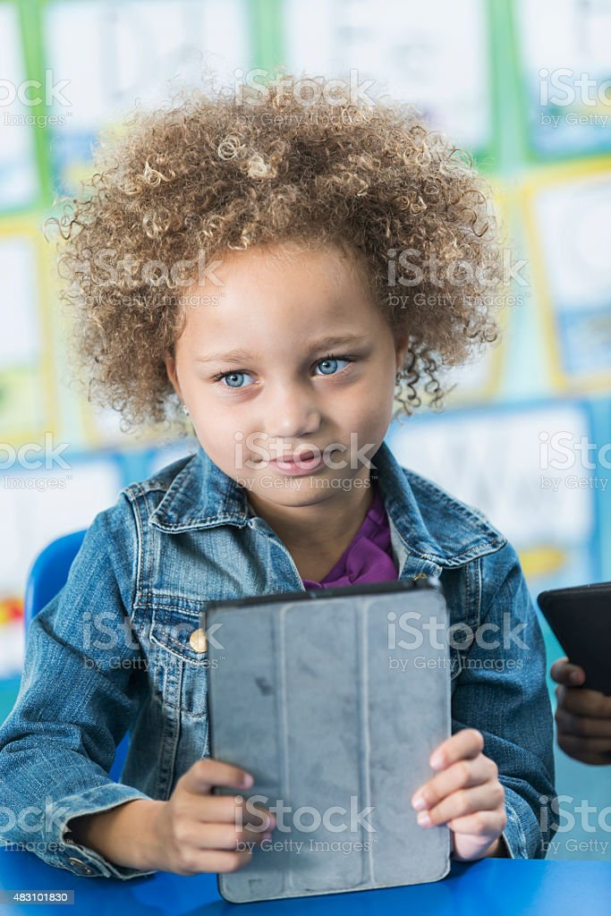 Cute mixed race girl in preschool with digital tablet stock photo