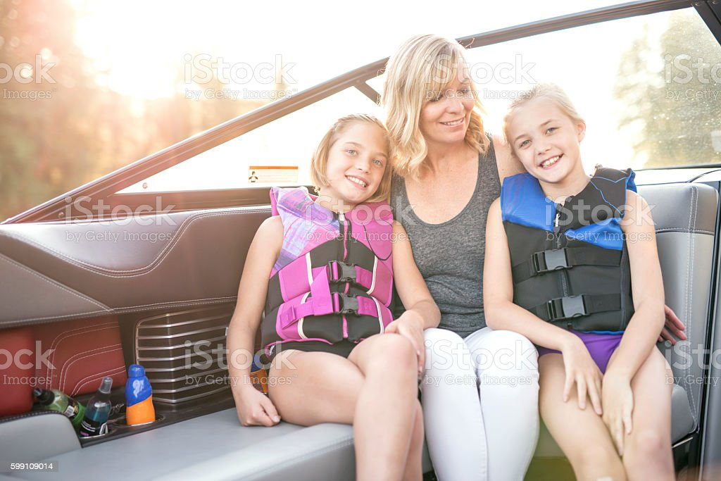 Cute mother and daughters sitting in a boat stock photo