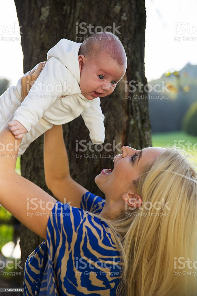 Cute mother and her baby boy playing in a park royalty-free stock photo