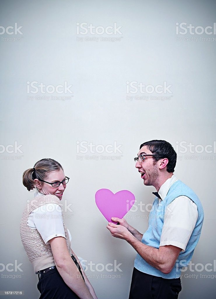 Cute Nerd Guy and Girl in Love Giving A Heart stock photo