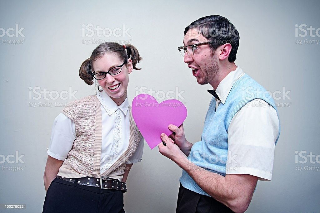 Cute Nerd Guy and Girl in Love Holding A Heart stock photo