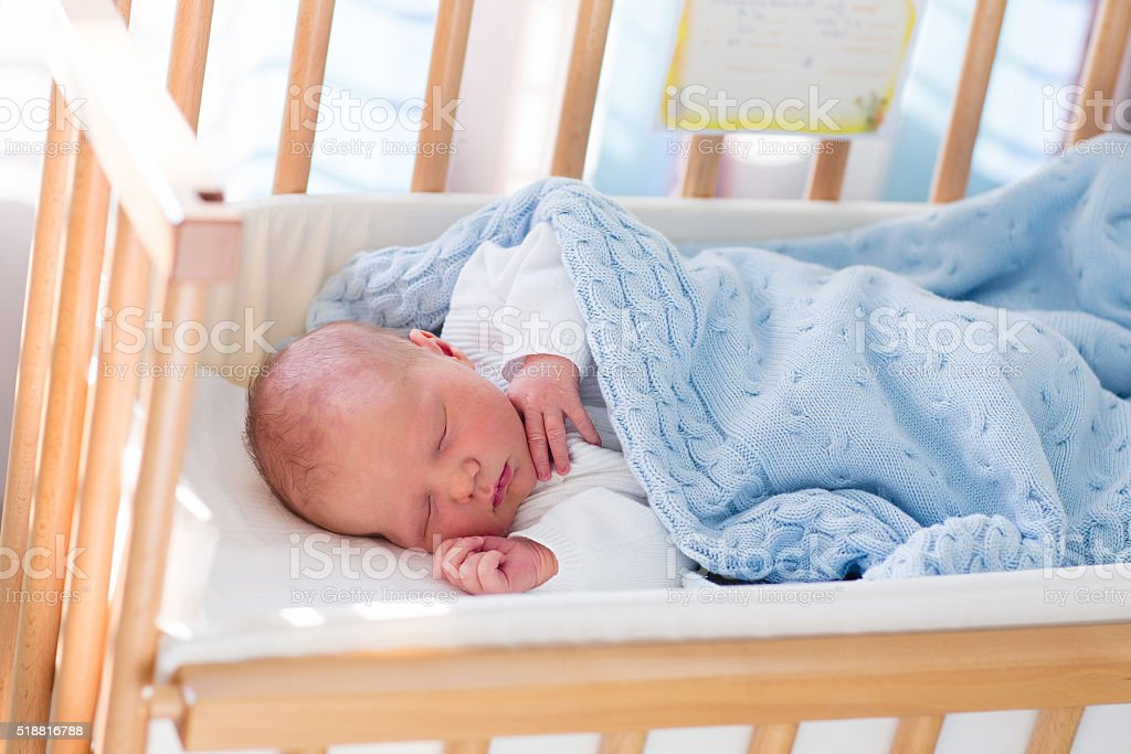 Cute newborn baby boy in hospital cot stock photo