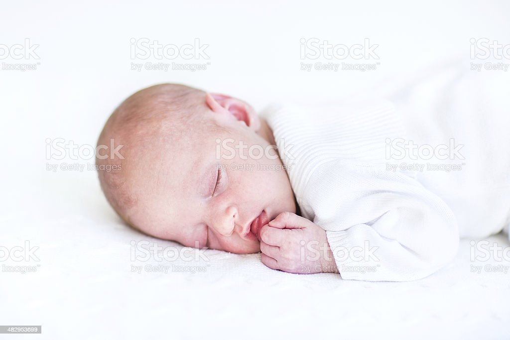 Cute newborn baby sleeping on a white knitted blanket stock photo