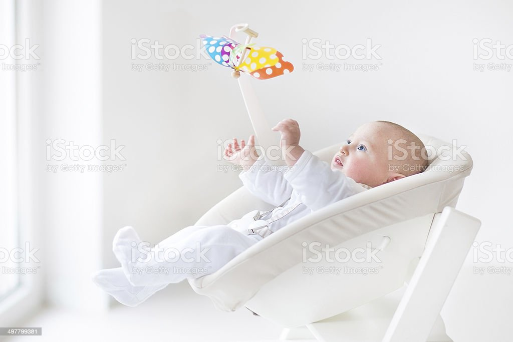 Cute newborn baby watching colorful mobile toy in white chair stock photo